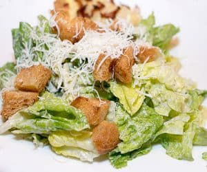 Romaine lettuce topped with a rich and creamy dressing, home-made croutons and shredded Parmesan cheese.
