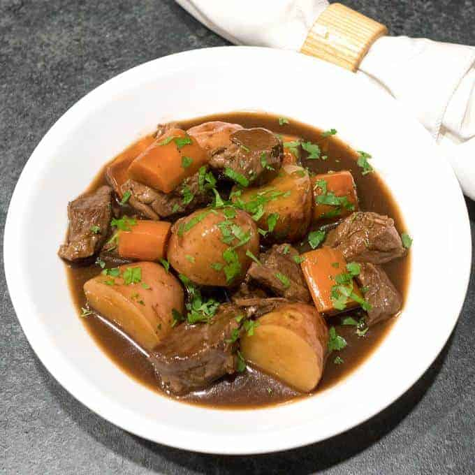 Slow Cooker Irish Guinness Beef Stew boasts tender chunks of beef with potatoes and carrots braised in a rich Guinness-infused gravy.