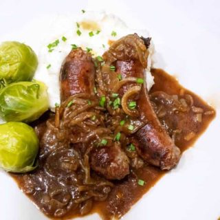 "Bangers and mash with onion gravy is traditional British pub fare. Bangers are so named because they used to pop or ""bang"" when cooked over high heat."