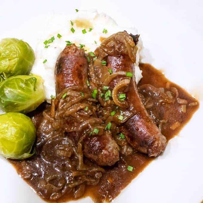 """Bangers and mash with onion gravy is traditional British pub fare. Bangers are so named because they used to pop or """"bang"""" when cooked over high heat."""