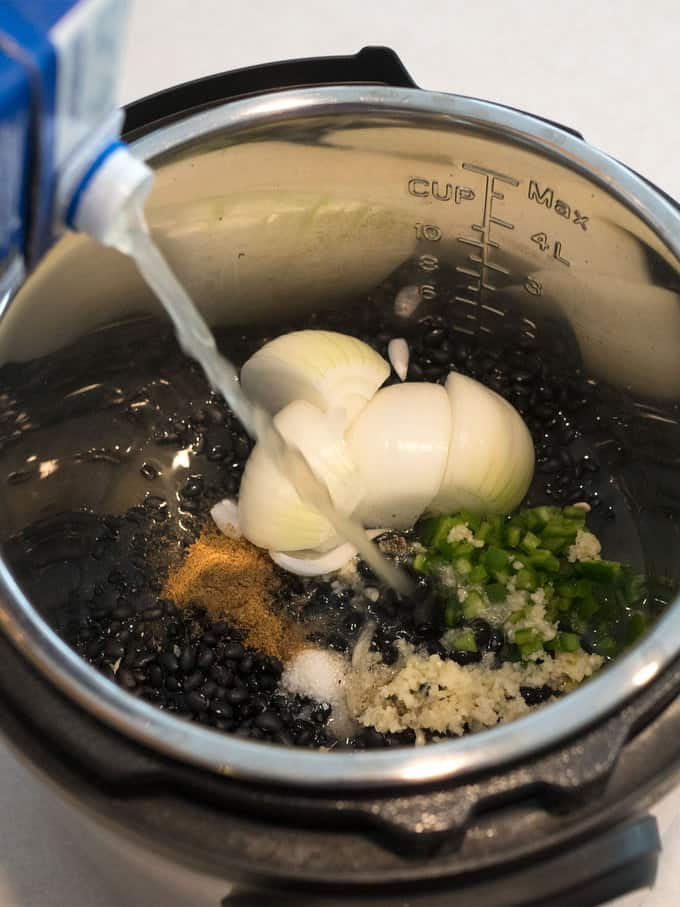 Adding all ingredients for smashed black beans to Instant Pot