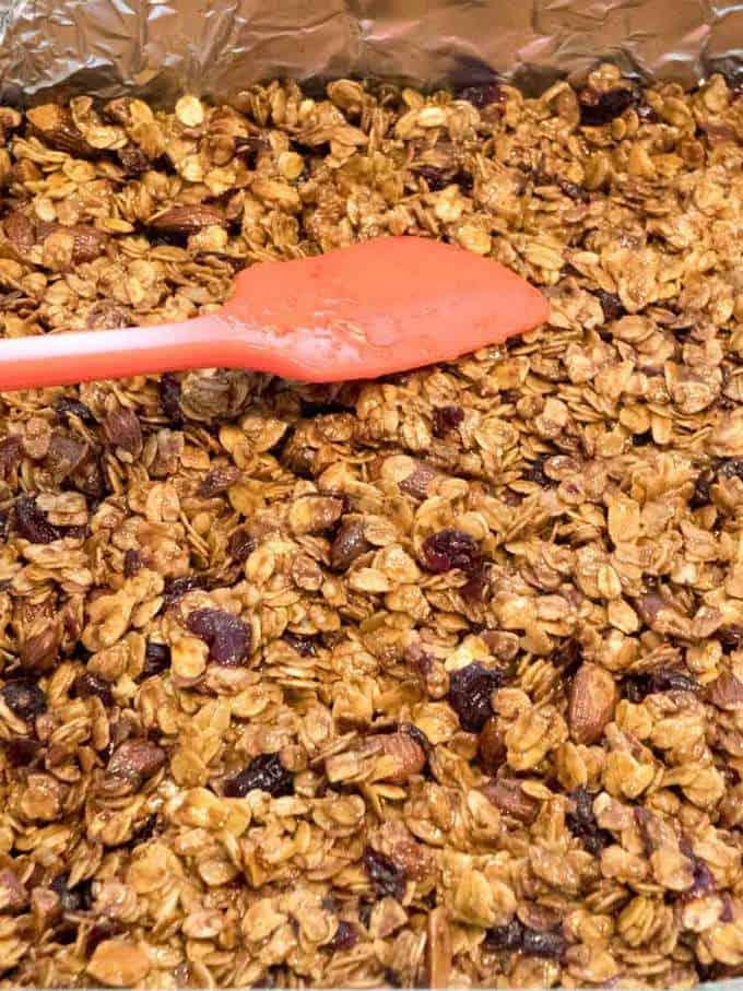 Pressing granola mixture into pan