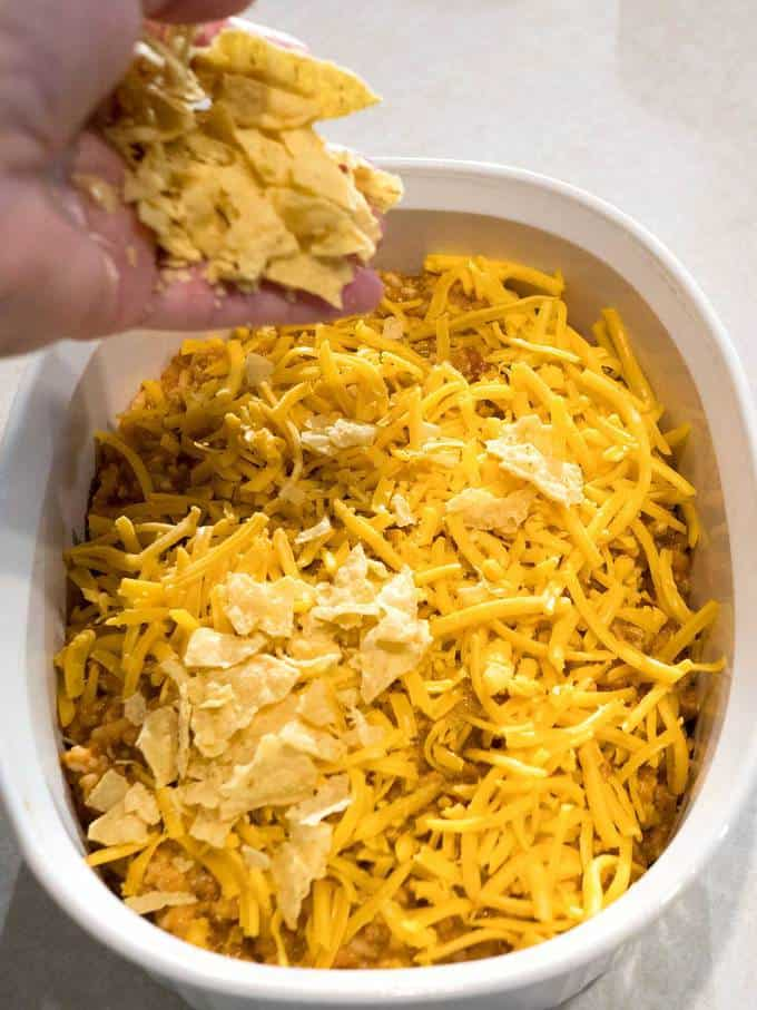 Sprinkling on cheese and crushed tortilla chips