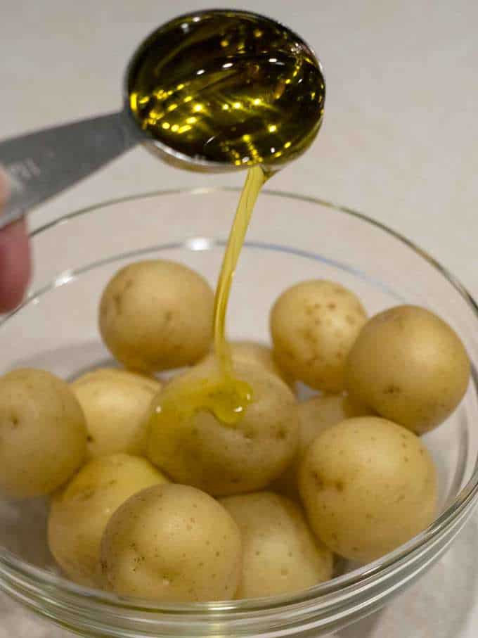 Drizzling olive oil on potatoes