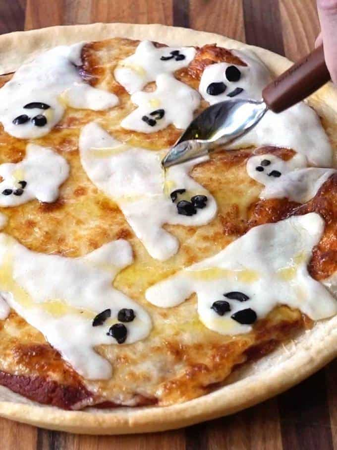 Drizzling Olive Oil on Halloween Ghost Pizza
