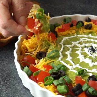 Spooky 8-Layer Taco Dip is the perfect appetizer and party food for all of your Halloween festivities.