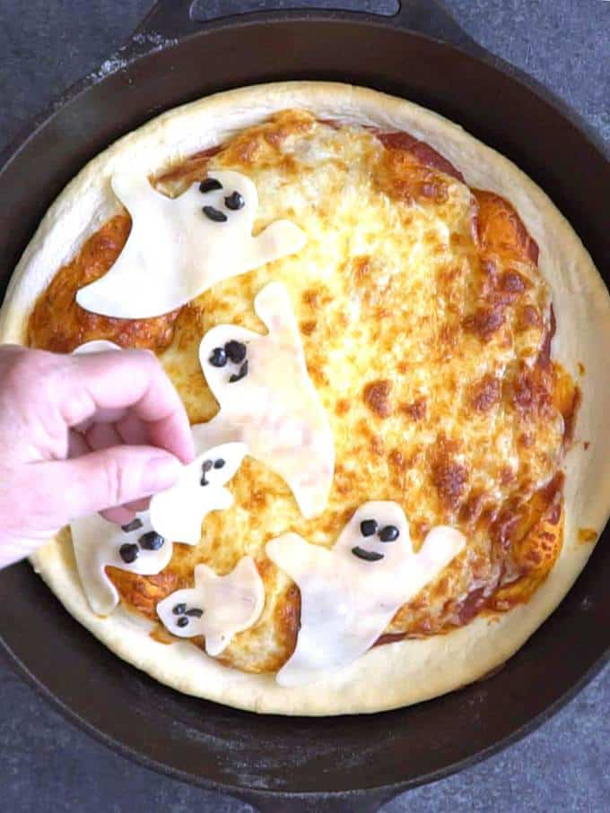Placing the Ghosts on the Halloween Cast-Iron Skillet Ghost Pizza