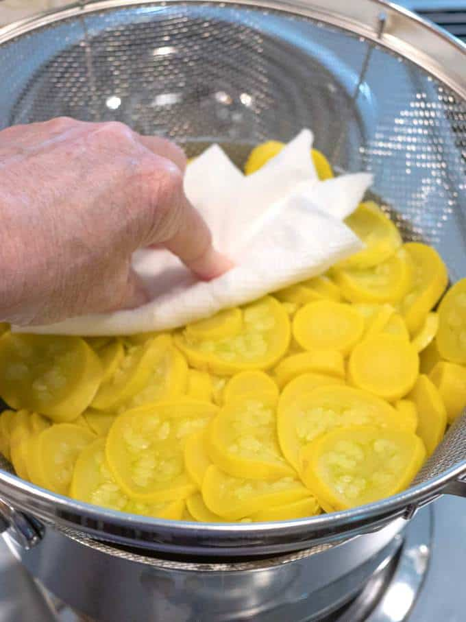 Pressing squash with paper towel to squeeze out water