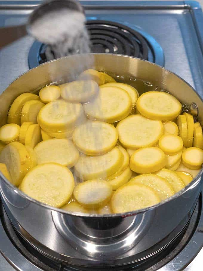 Adding salt to water to cook the squash