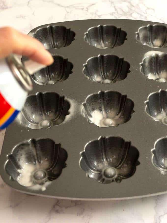 Spraying mini-bundtlette pan with vegetable spray mixed with flour