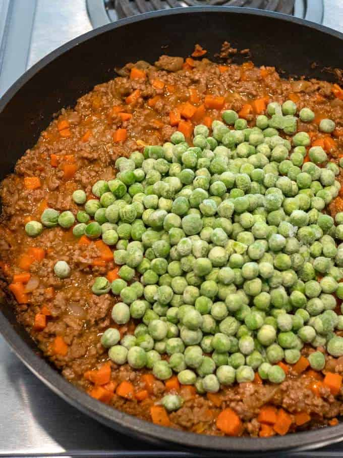Adding Green Peas to Cottage Pie mixture.