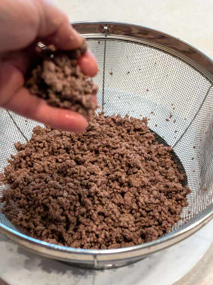 Breaking up cooked ground beef with hands
