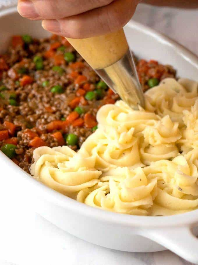 Piping the mashed potatoes onto the meat mixture for the cottage pie