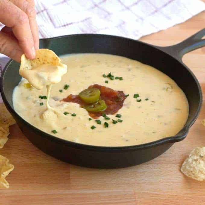 Dipping Tostidos Scoop in White Queso Dip