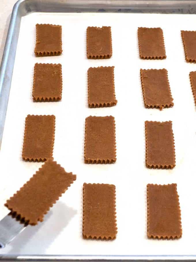 Placing cut cookie dough onto parchment lined baking sheet