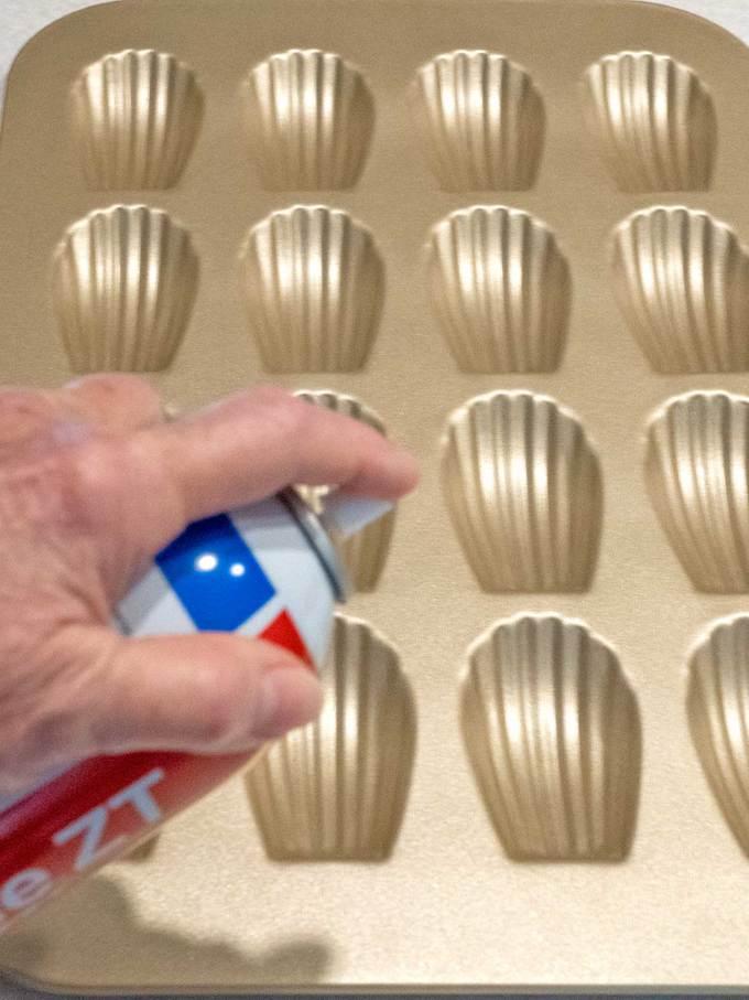 Spraying Madeleine pan with non-stick spray