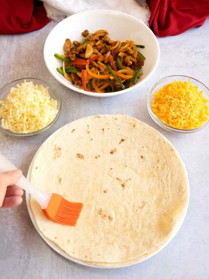 Brushing flour tortilla with oil