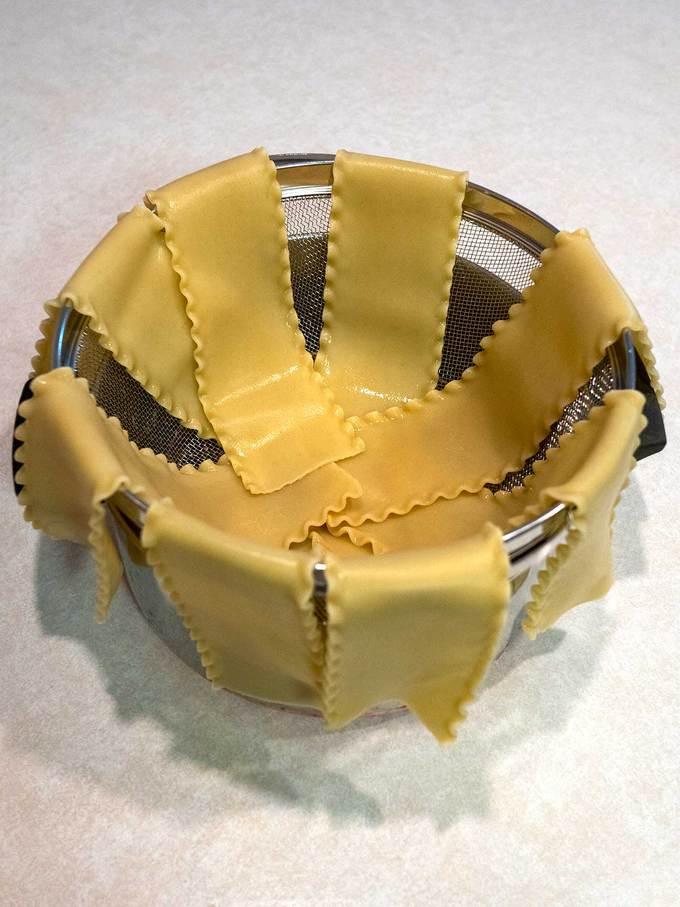 Cooked lasagna noodles draped on colander to keep separated