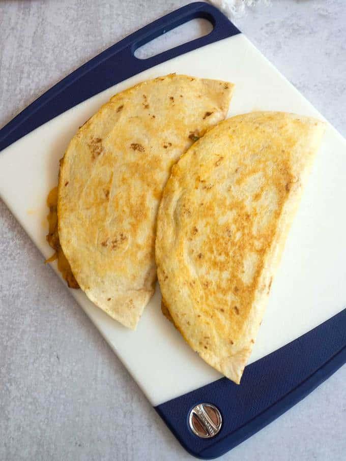 Chicken Fajita quesadillas cooling on cutting board.