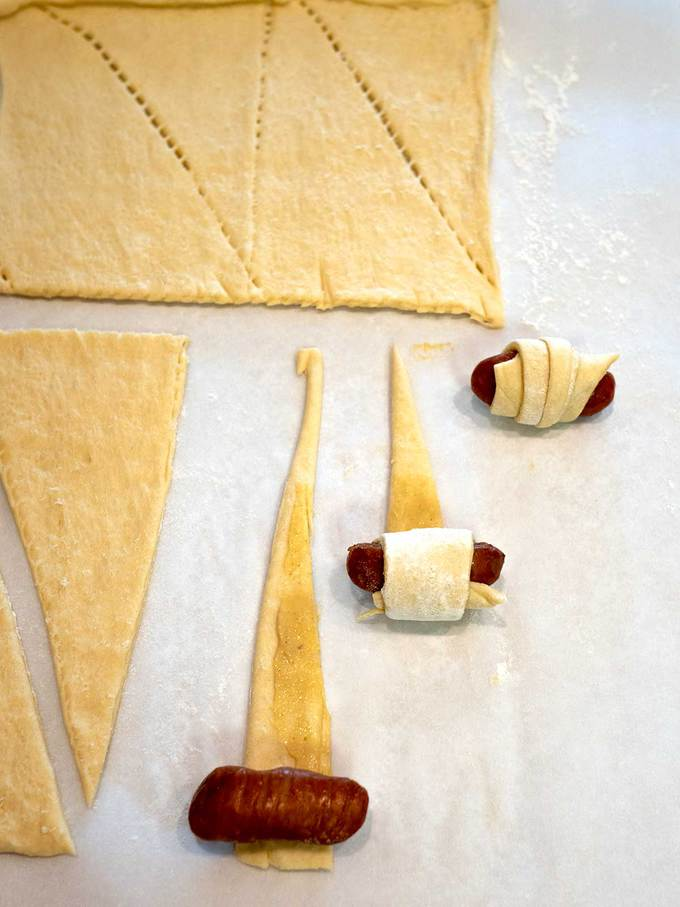 Rolling the crescent roll triangles around the Cocktail smokies