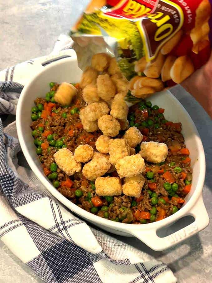 Adding tater tots to meat mixture