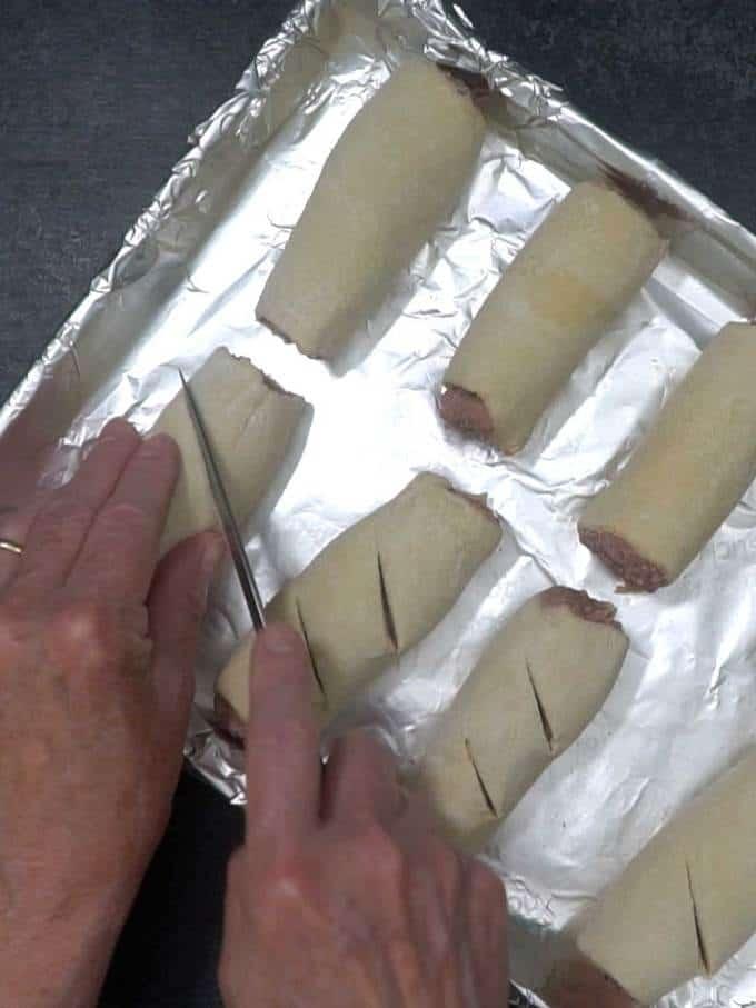 Cutting slits in sausage rolls