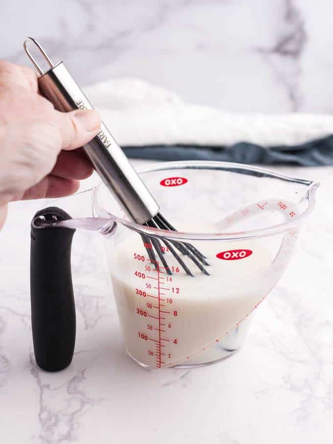 Whisking together sour cream and chicken broth