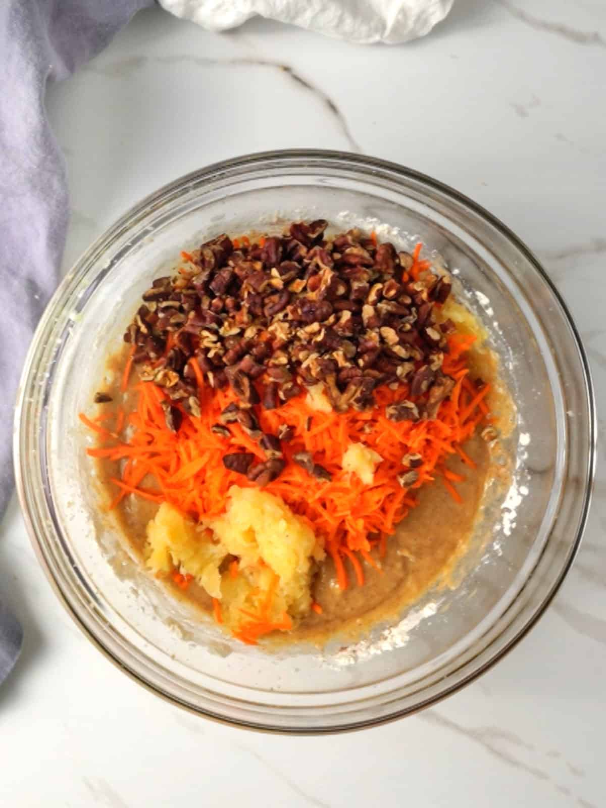 Adding carrots, pineapple and pecans to batter.