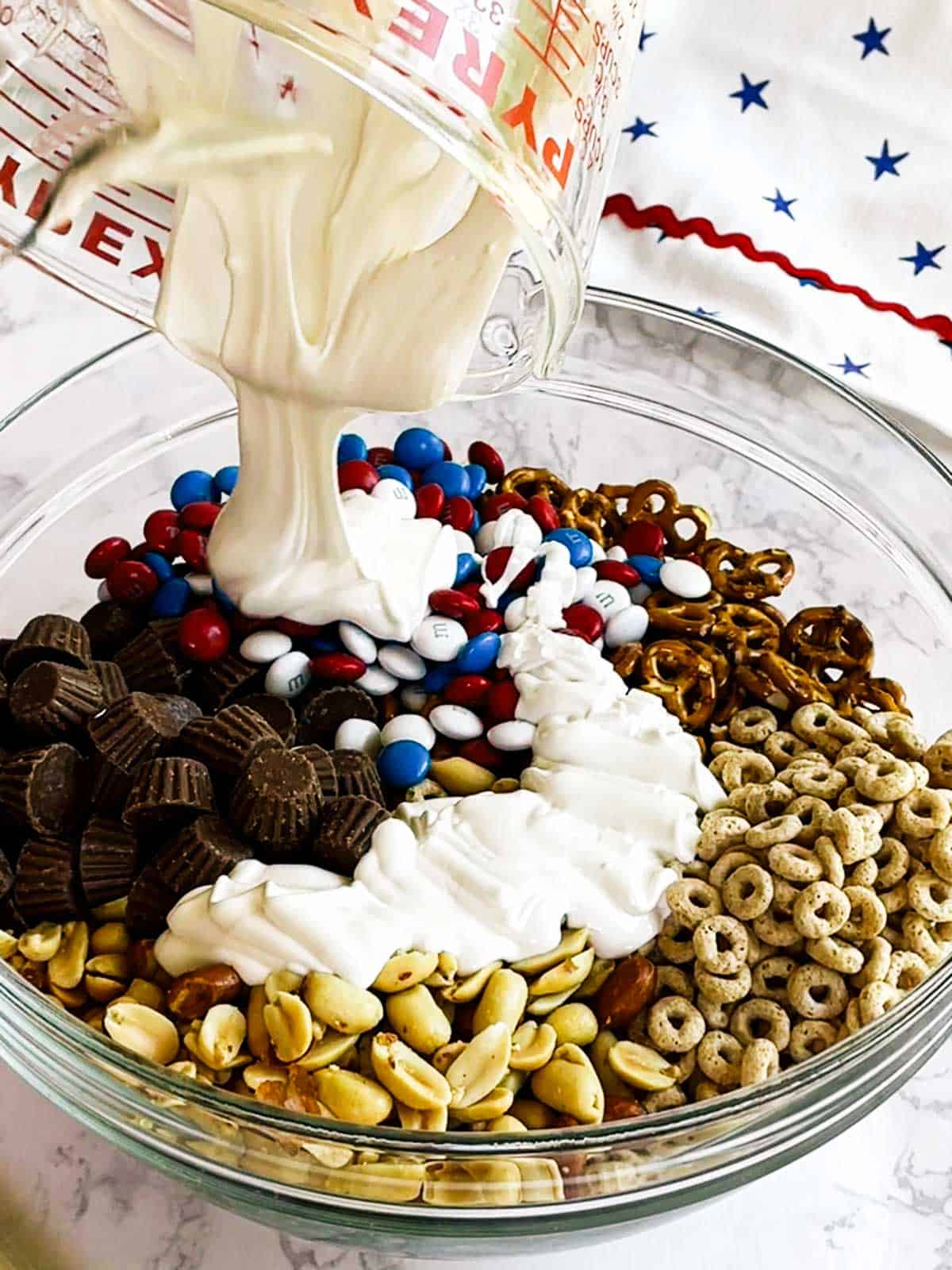 Adding melted white candy melts to snack mix ingredients.