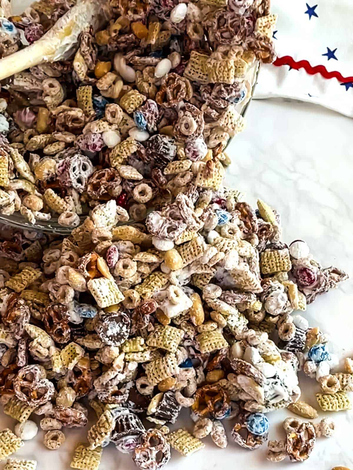 Dumping the coated snack mix onto parchment paper