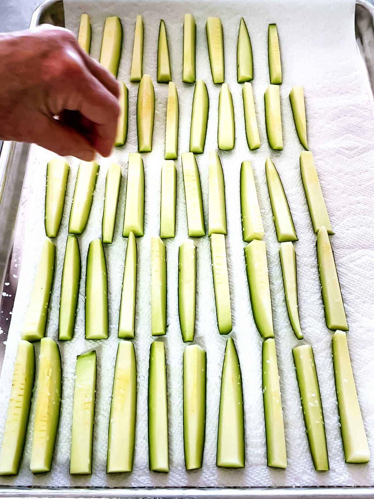 Sprinkling salt on zucchini sticks