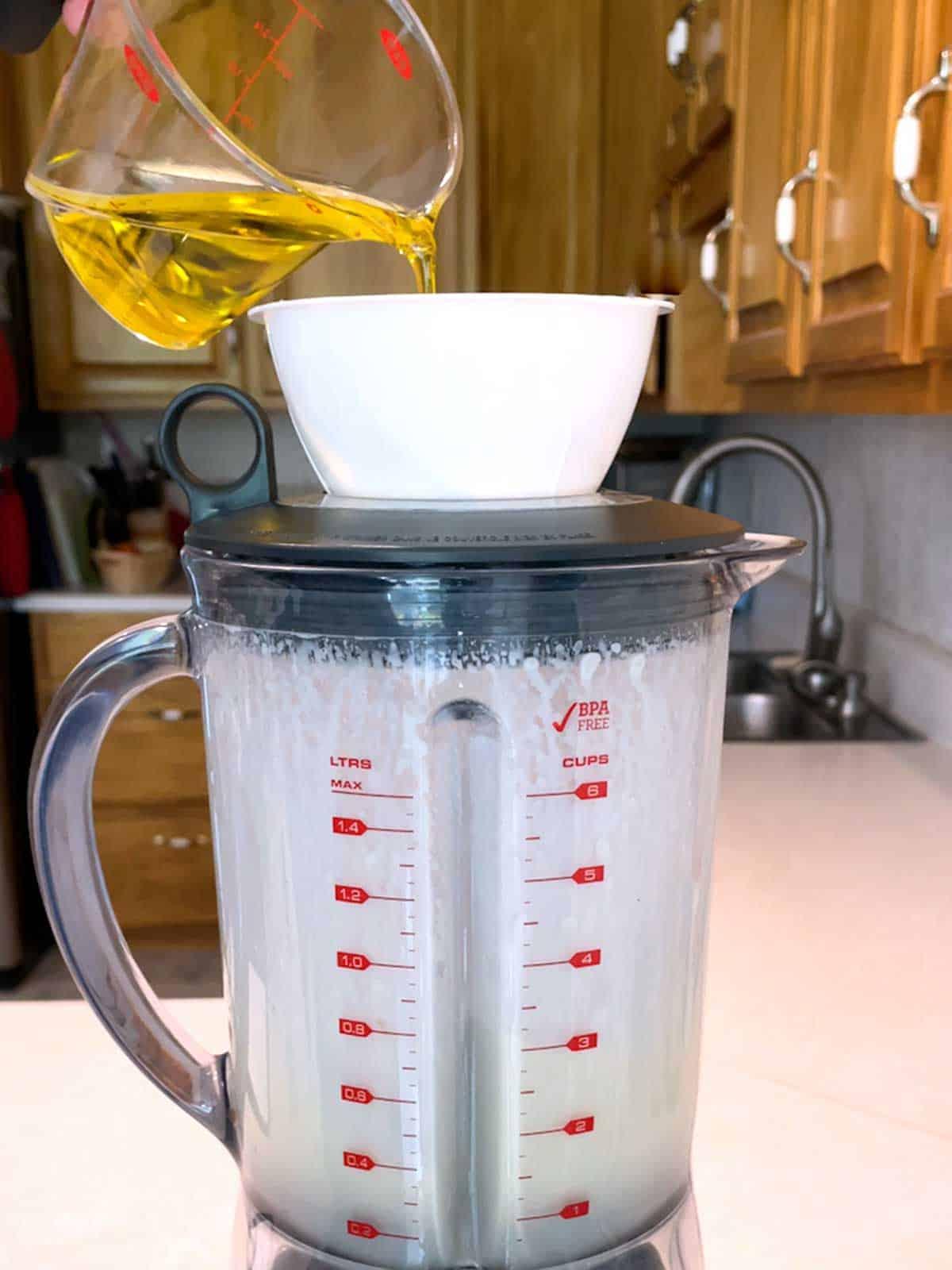 Adding olive oil to the blender for the dressing.