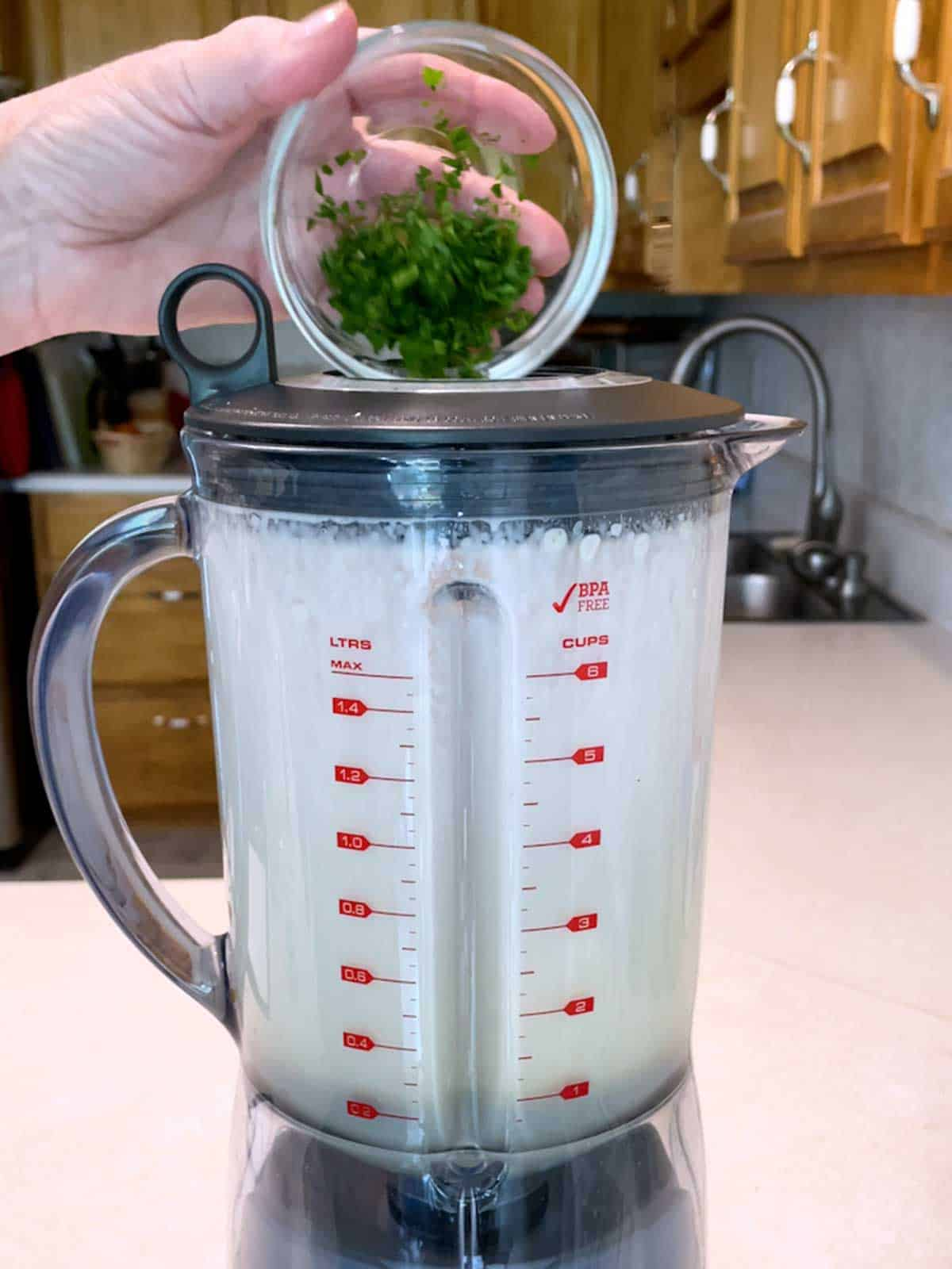 Adding parsley to the blender for the dressing.