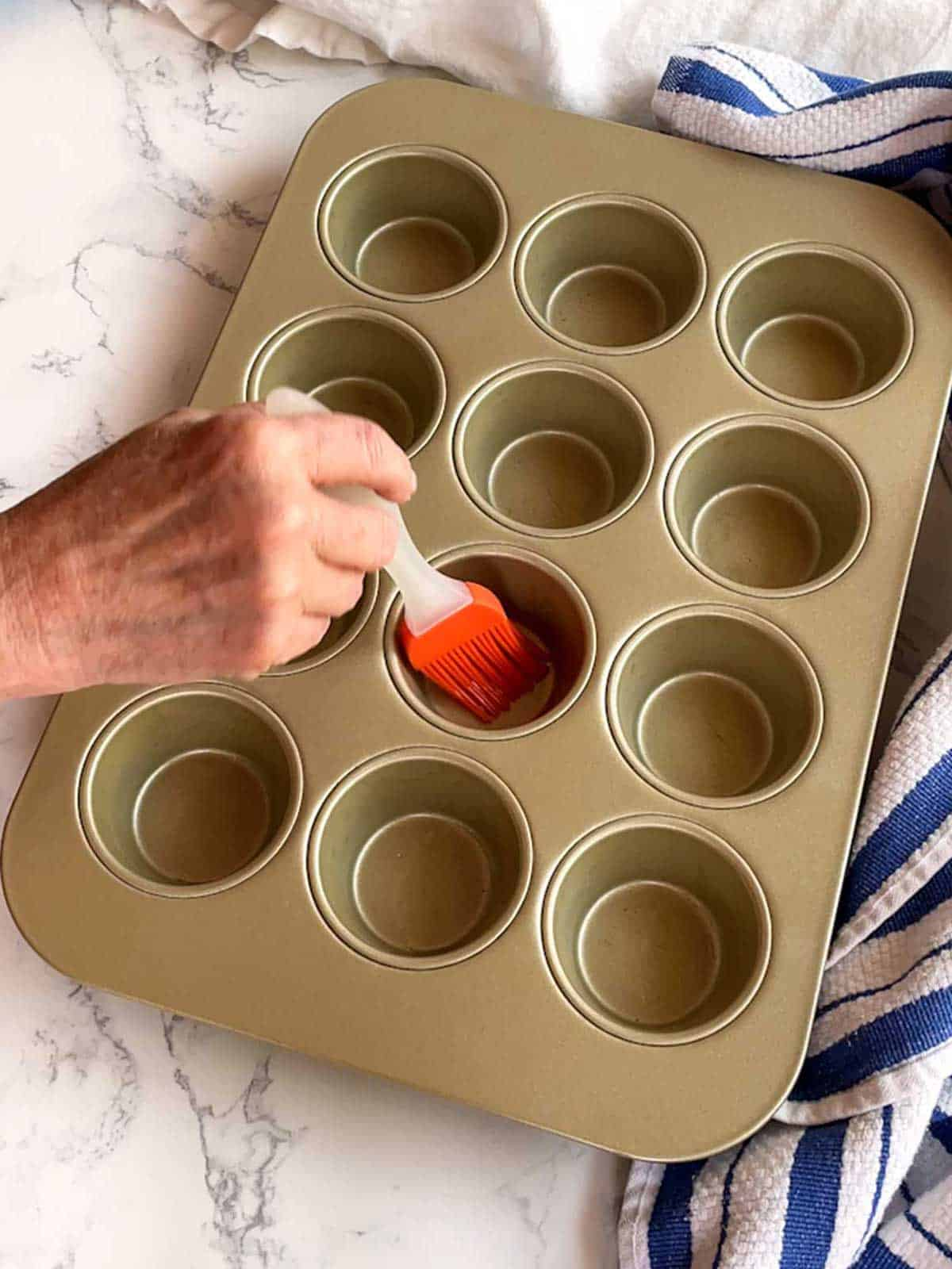 Brushing muffin pan with vegetable oil