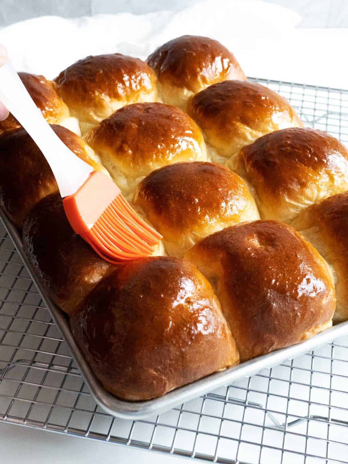 Brushing the cooked rolls with melted butter.