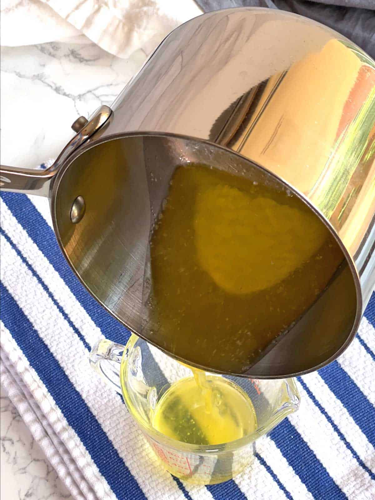 Pouring Clarified Butter into measuring cup.