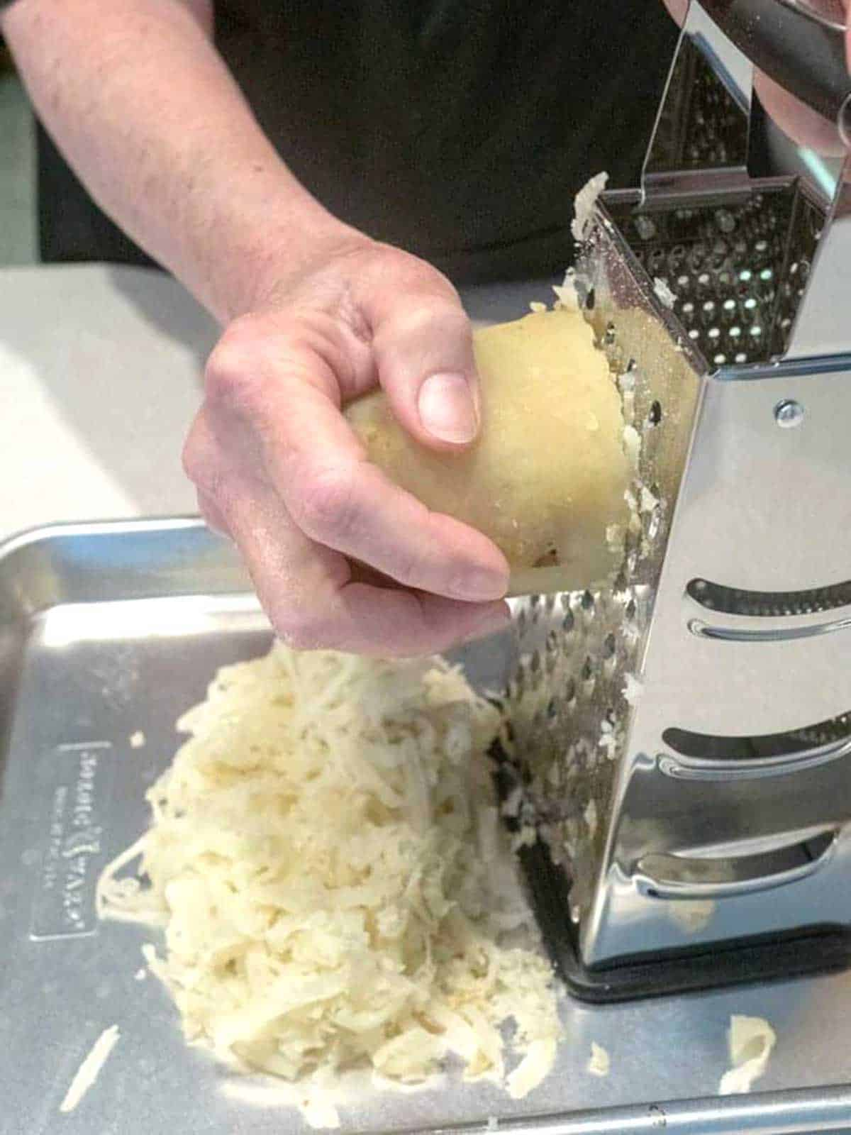 Grating potatoes with box grater.