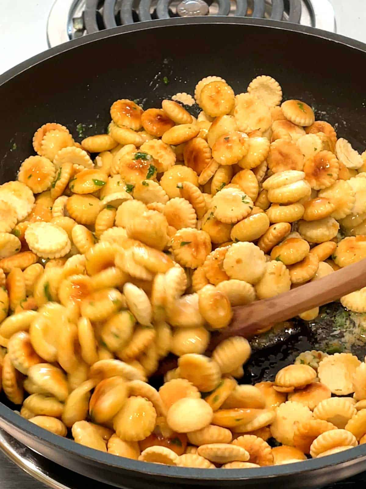 Stirring oyster crackers with butter mixture.