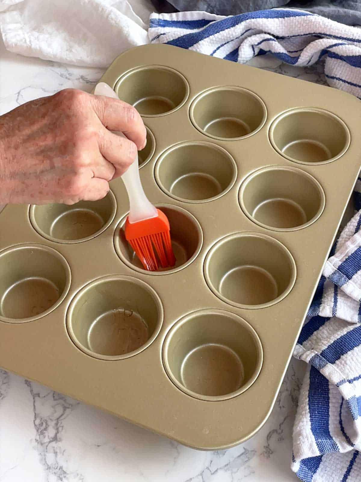 Brushing the muffin tin.