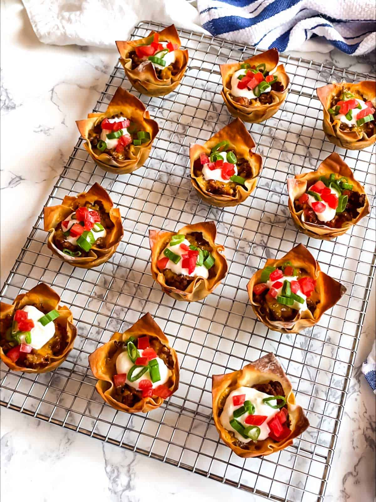 Tasty Taco Cups garnished with sour cream, green onion tops and diced tomatoes.