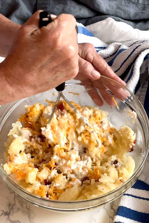 Using potato masher to combine ingredients.