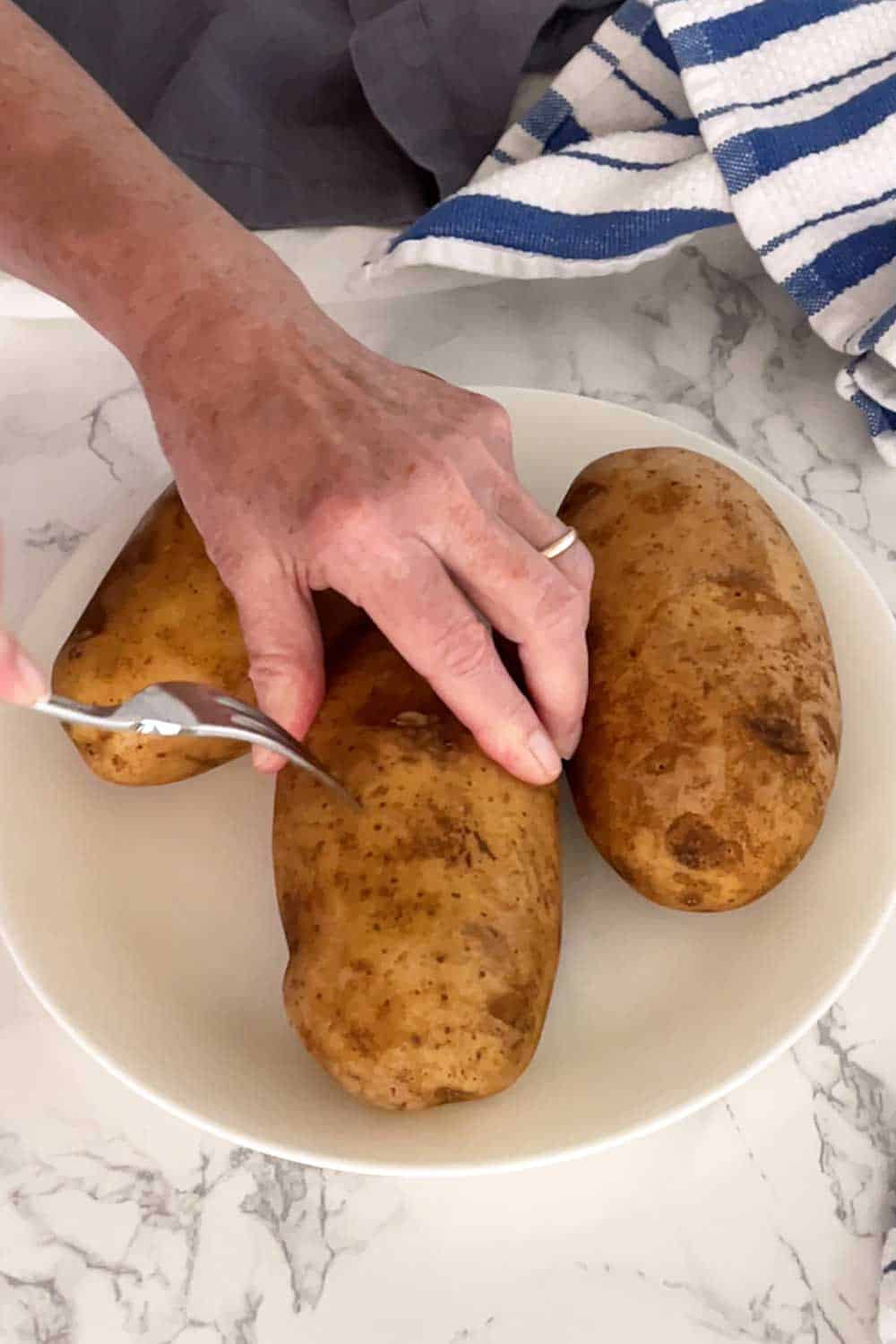 Piercing the potatoes with a fork.