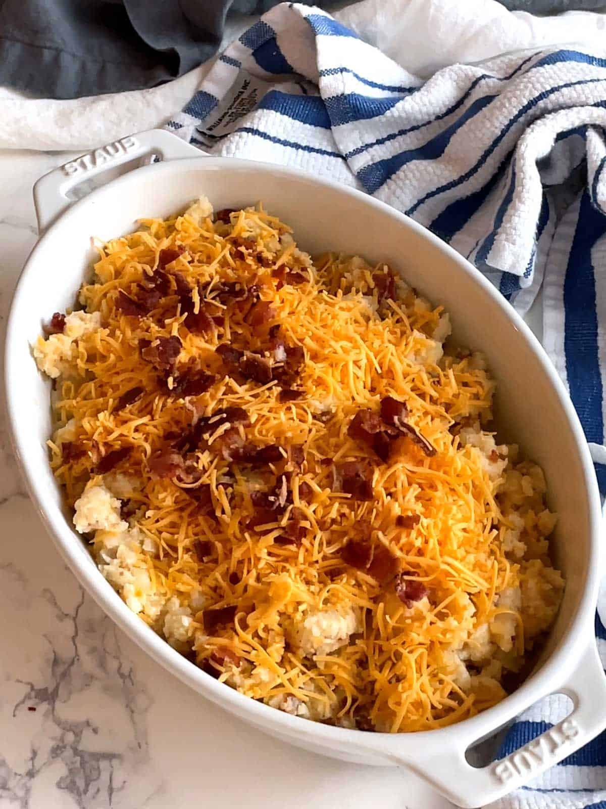 Sprinkling cheese and bacon on casserole.