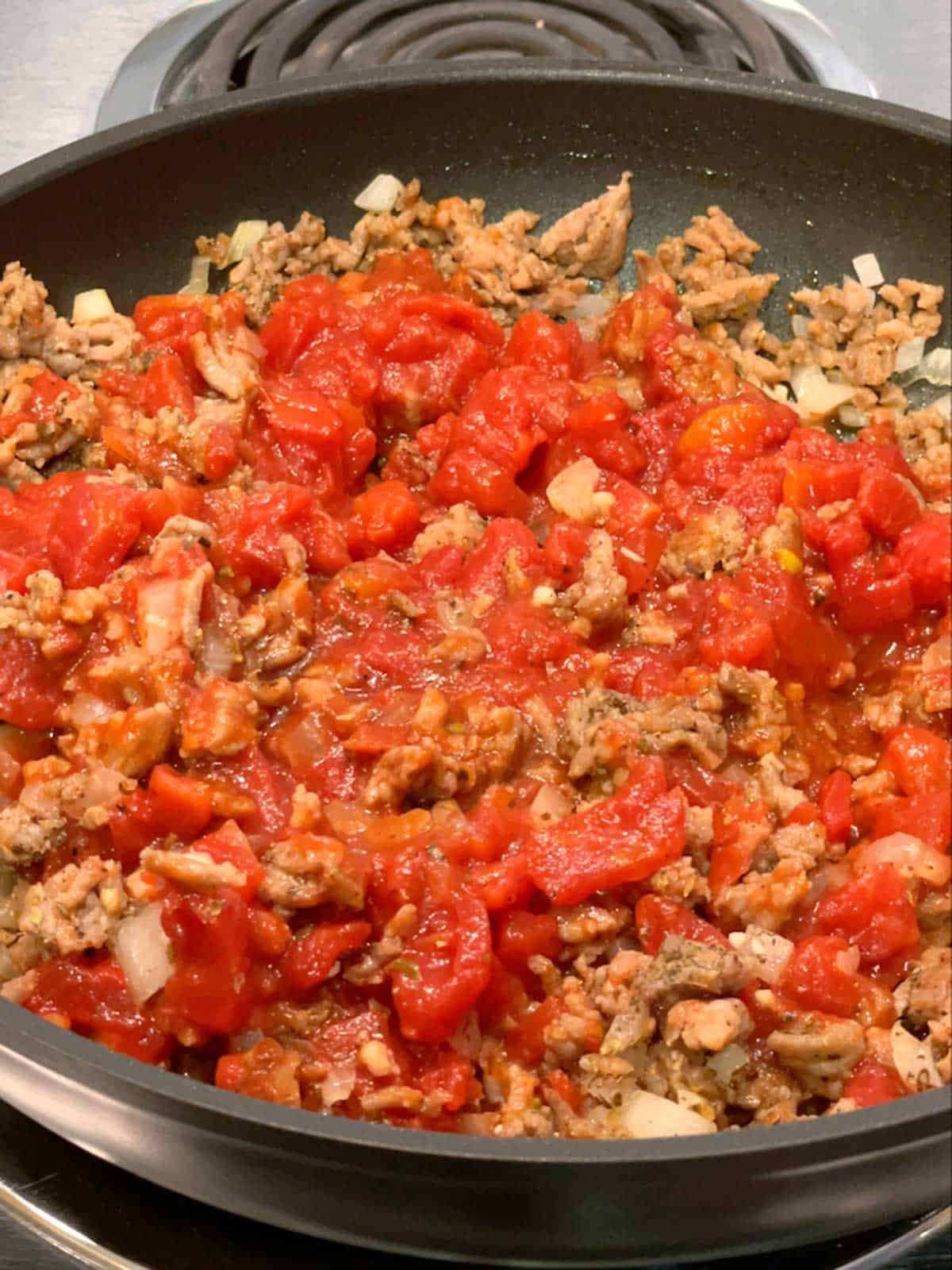 Petit diced tomatoes, tomato sauce and tomato paste added to the sausage mixture.