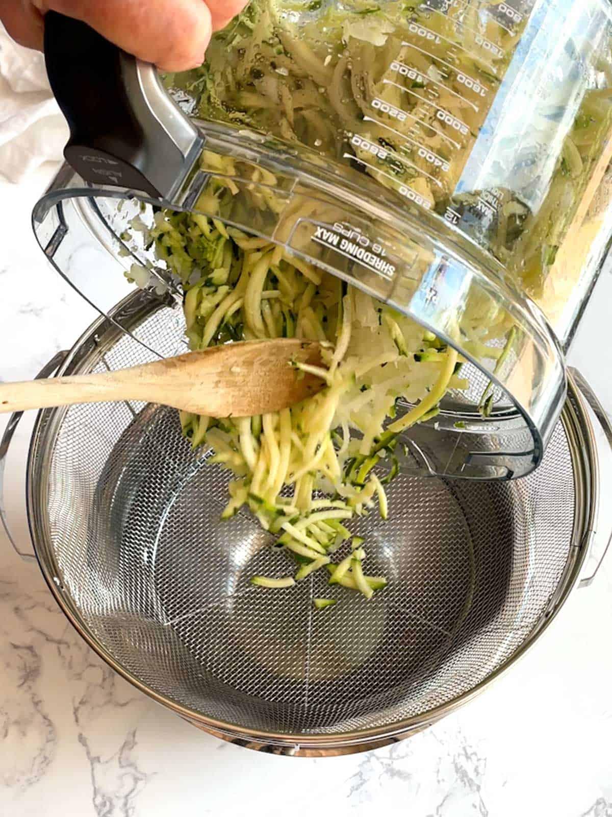 Transferring zucchini to wire mesh strainer.