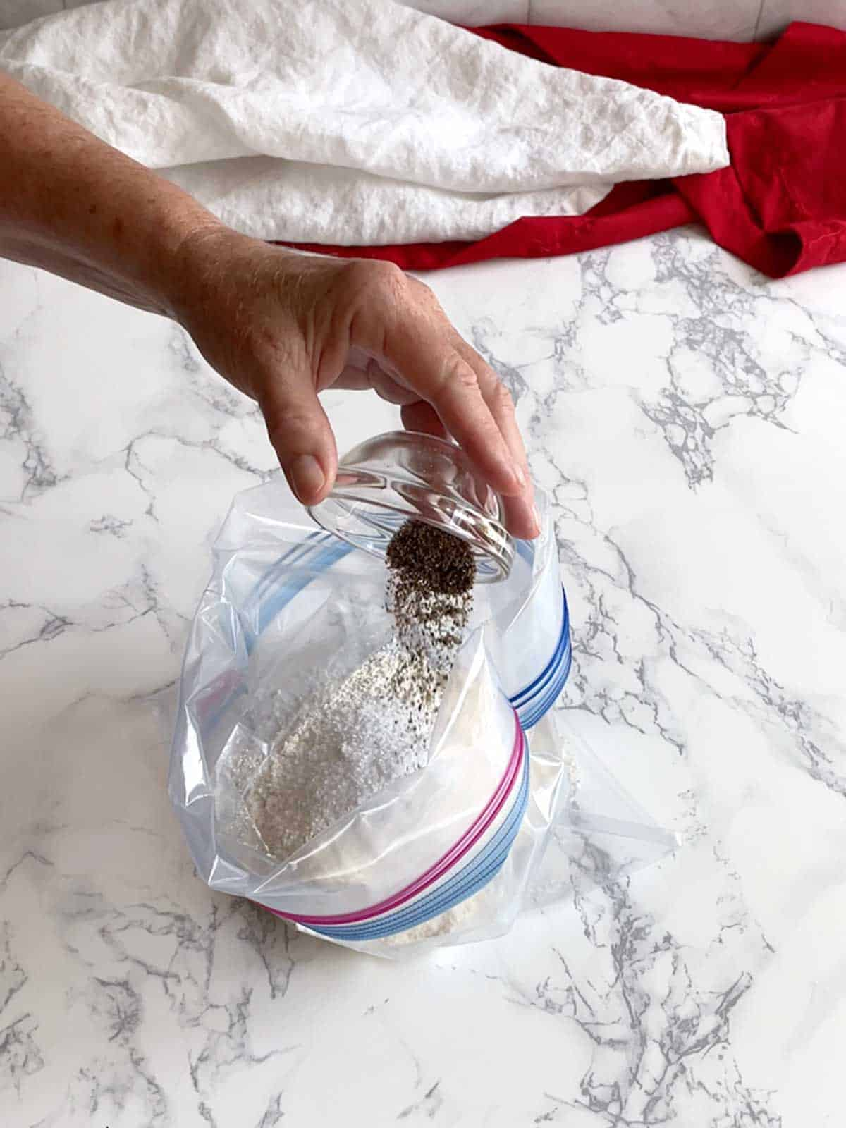 Adding pepper to Ziploc bag with flour and salt.