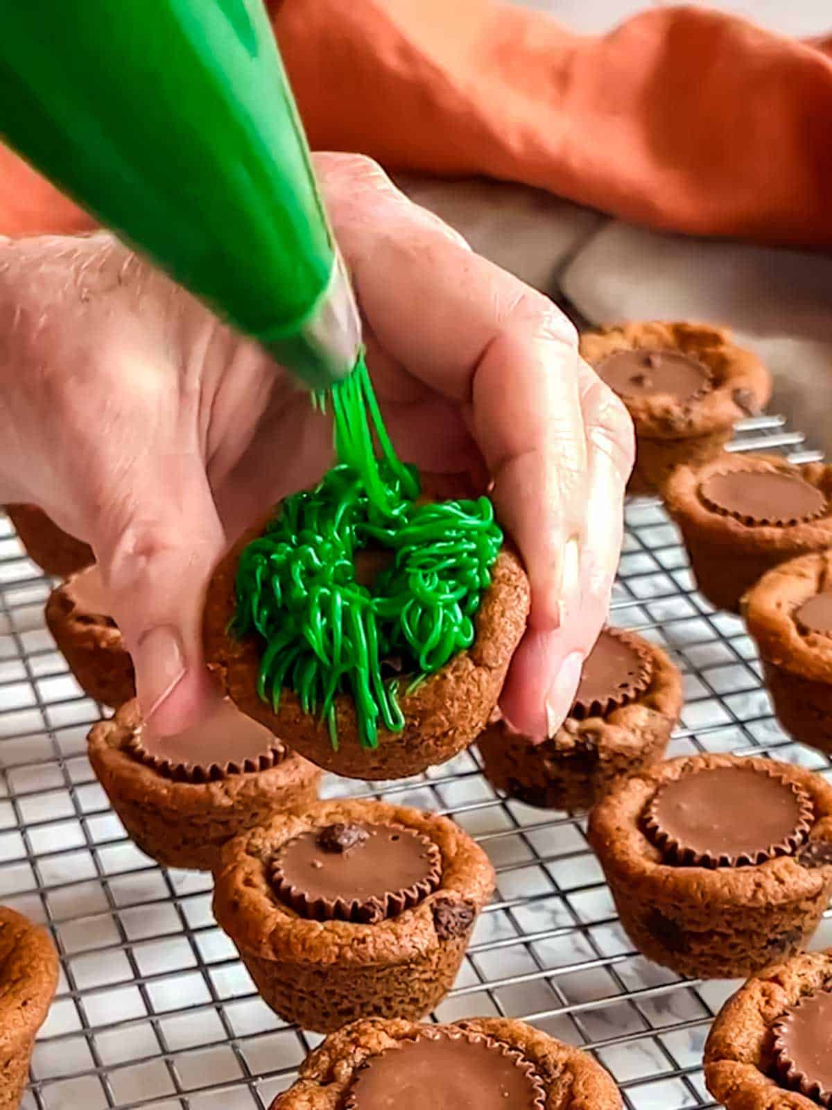 """Piping """"grass"""" onto cookie cup."""