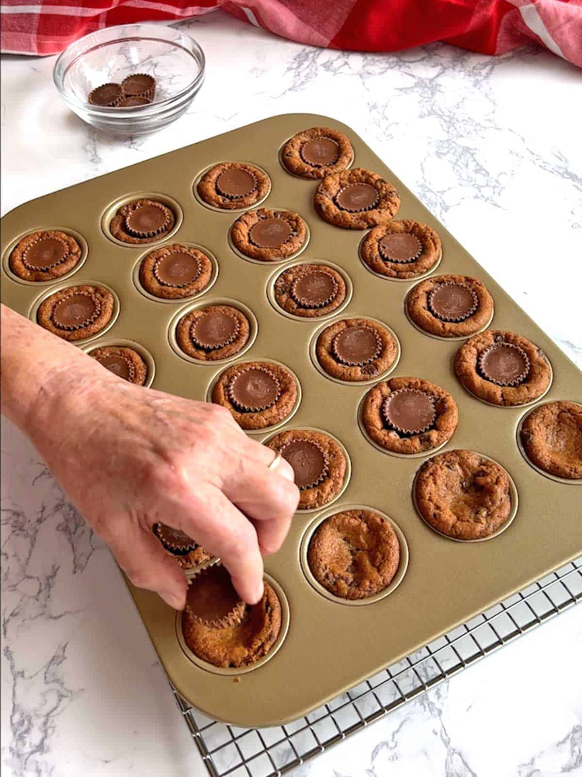 Placing Reese's Miniatures in cookie cups.