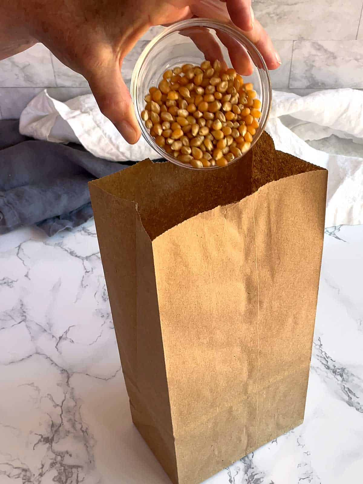 Adding popcorn to the brown paper bag.