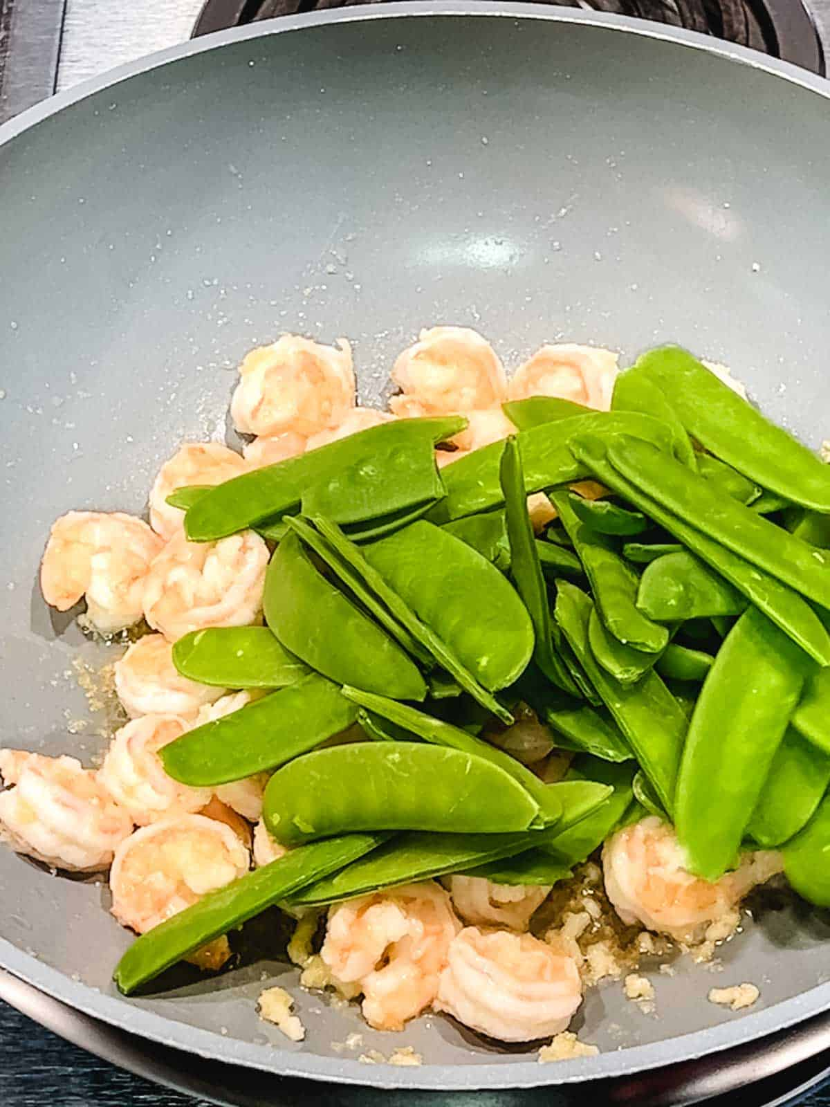 Adding the snow peas to the shrimp in the wok.